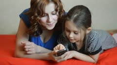mother and daughter pressed a button on a mobile phone - stock footage