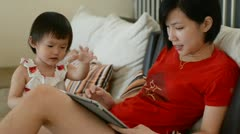 Stock Video Footage of mother and daughter playing tablet at living hall