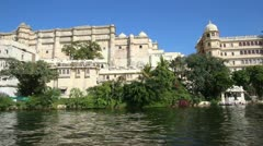 View from boat on lake and palaces in Udaipur India Stock Footage