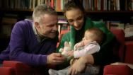 Happy family portrait, wife and husband playing with baby at home Stock Footage