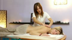 Beautiful blonde woman relaxes during massage at the health spa Stock Footage