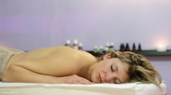 beautiful blonde girl relaxes during massage at the health spa - stock footage