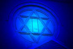 Magic blue light over jewish star on vintage church, stone wall details Stock Photos