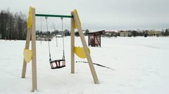 Empty colorful swing seat move winter snow beach playground Stock Footage