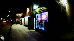 Man Exits Smoke Shop Toward Camera- Night Stock Footage