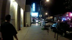 Two Men Walk Street With Retro Theater And Shops- Night Stock Footage