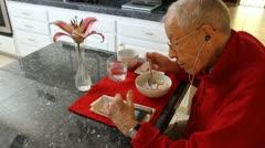Hip Elderly Man eating Breakfast alone listening to iPhone  Stock Footage