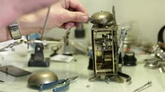 Watchmaker assemble a antique clock Stock Footage
