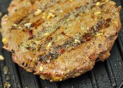 Hamburger on a grill Stock Photos