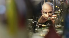 Watchmaker checks the operation of a old clock Stock Footage