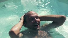 Man relaxing in swimming pool, slow motion shot at 240fps Stock Footage