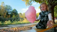 Child eating cotton candy in the park Stock Footage