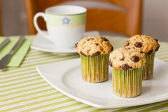 Chocolate chip muffins on white plate and green striped tablecloth Stock Photos