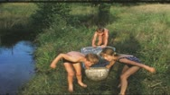 Stock Video Footage of Vintage 8mm film: Children in bathtub on pond, 1960s