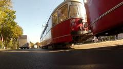 Low angle in motion shot of the car driving on Vienna ring with tram Stock Footage