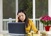 Mature woman stressed while working at home Stock Photos