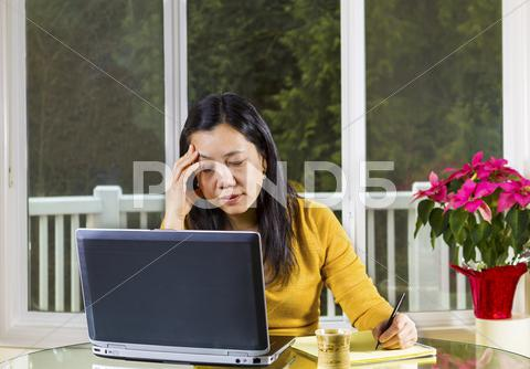 Stock photo of mature woman stressed while working at home