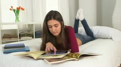 Young Caucasian student studying on her bed Stock Footage
