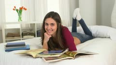 Young Caucasian student smiling with books on her bed Stock Footage