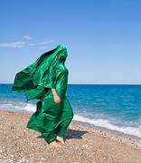 Girl silhouette under green tissue on the sea beach Stock Photos