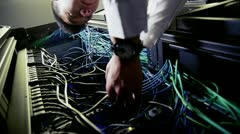 IT engineer working on server wiring in a data centre - stock footage