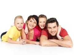 happy family with two children lying on white floor - stock photo