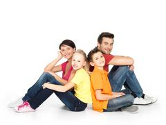 Stock Photo of happy  family with two children sitting on white floor