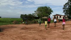 People walking through village in Amazon rain forrest - stock footage