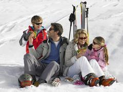 Young family sharing a picnic on ski vacation Stock Photos