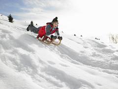 Pre-teen boy on a sled in the snow Stock Photos