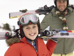 Pre-teen boy with father on ski vacation Stock Photos