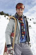 Stock Photo of young man carrying sled in alpine landscape