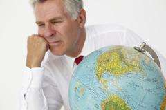 Senior businessman with globe - stock photo