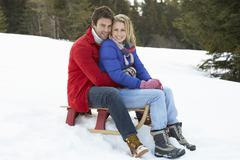 young couple on a sled  in alpine snow scene - stock photo