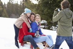 Young family sitting on a sled in the snow Stock Photos