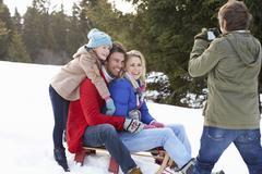Nuori perhe istuu kelkka lumessa Kuvituskuvat