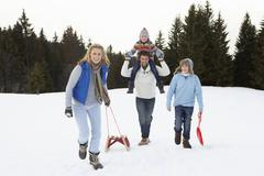 Young family walking through snow with sled Stock Photos