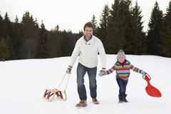Nuori isä ja tytär kävely lumessa kelkat Kuvituskuvat