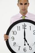 Young businessman with giant clock Stock Photos