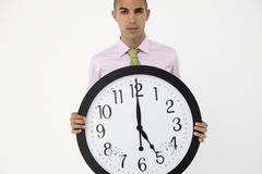 Young businessman with giant clock - stock photo