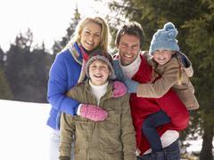 young family  in alpine snow scene - stock photo