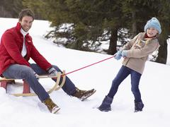 young girl pulling father through snow on sled - stock photo