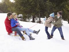 Stock Photo of young girl and boy pulling parents through snow on sled