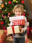 Young child holding gifts in front of christmas tree Stock Photos