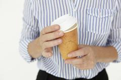 Businesswoman holding takeout coffee - stock photo