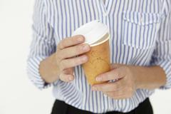 Businesswoman holding takeout coffee Stock Photos