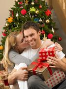 Young couple with gifts in front of christmas tree Stock Photos