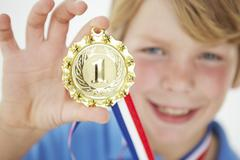 Young boy showing off medal Stock Photos