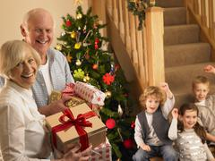 Senior couple with grandchildren at christmas Stock Photos