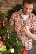 young man fixing christmas tree lights - stock photo